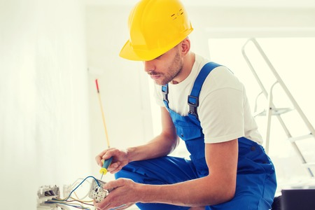 cable: building, renovation, technology, electricity and people concept - builder with screwdriver fixing socket indoors