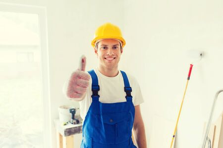 boilersuit: building, repair, gesture and people concept - smiling young builder in hardhat showing thumbs up indoors