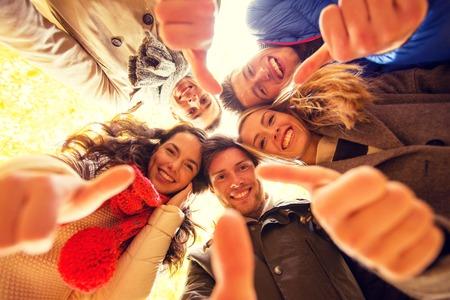 Liebe, Freundschaft, Geste, Saison und Menschen Konzept - Gruppe von Männern und Frauen lächelnd Thums up im Herbst Park zeigt Standard-Bild