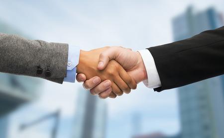 hand shake: negocios y concepto de la oficina - hombre de negocios y empresaria agitando las manos