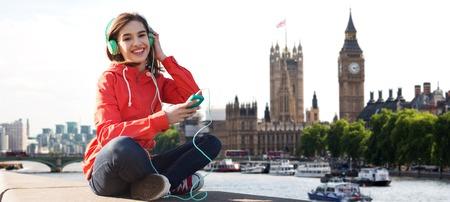 personas escuchando: tecnología, viajes, turismo, vacaciones y la gente concepto - mujer joven o adolescente con el teléfono inteligente y los auriculares escuchando música a través de la ciudad y Thames Londres de fondo, sonriendo río