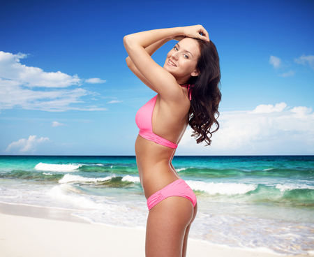 sexy pose: people, summer holidays, travel, tourism and beach concept - happy young woman posing in pink bikini swimsuit over sea shore and blue sky background Stock Photo