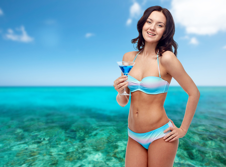 people, summer holidays, travel, tourism and alcohol drinks concept - happy young woman in bikini swimsuit holding glass of cocktail at beach party over sea and blue sky background
