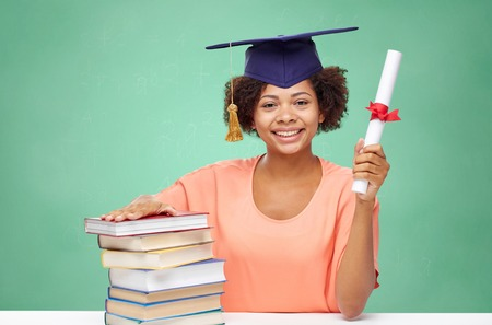 alumnos en clase: education, school, knowledge, graduation and people concept - happy smiling african american student girl in bachelor cap with books and diploma over green chalk board background