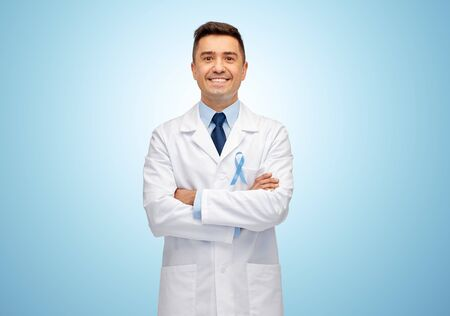 oncologist: healthcare, profession, people and medicine concept - smiling male doctor in white coat with sky blue prostate cancer awareness ribbon