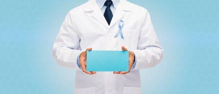 bata blanca: cuidado de la salud, la publicidad, la gente y concepto de la medicina - Cierre de médico masculino en bata blanca con la cinta de la conciencia del cáncer de próstata cielo azul que sostiene el papel en blanco Foto de archivo