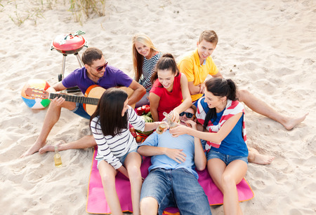 nonalcoholic beer: summer holidays, vacation, music, happy people concept - group of happy friends having picnic and playing guitar on beach, drinking non-alcoholic beer or soda lemonade