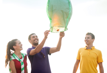 sky lantern: summer holidays, vacation, celebration and people concept - group happy friends with chinese sky lantern on beach Stock Photo
