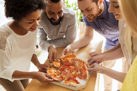 Zaken, voedsel, lunch en mensen concept - business team graag pizza eten in het kantoor Stockfoto - 57448257