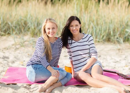chilling out: summer holidays, vacation and people concept - happy teenage girls or young women resting on beach