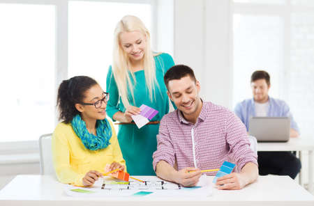 color samples: education, interior design and office concept - smiling interior designers with color samples and blueprint in office Stock Photo