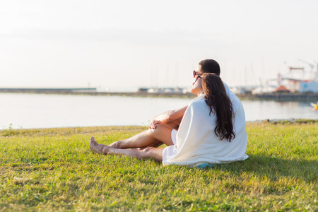 couple dating: love, summer, dating and people concept - close up of happy couple sitting on grass at seaside