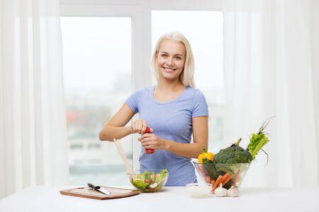 sal: una alimentación sana, comida vegetariana, la dieta y el concepto de la gente - mujer joven cocina ensalada de verduras en su casa sonriendo