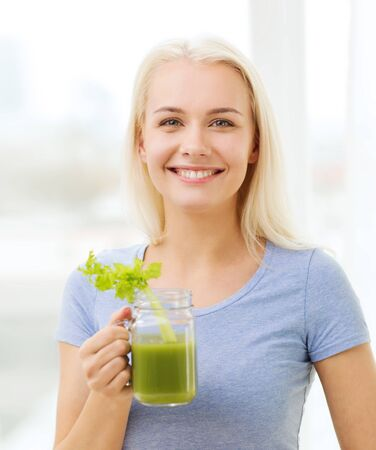 health woman: healthy eating, vegetarian food, dieting, detox and people concept - smiling woman drinking green vegetable juice or shake from glass at home Stock Photo