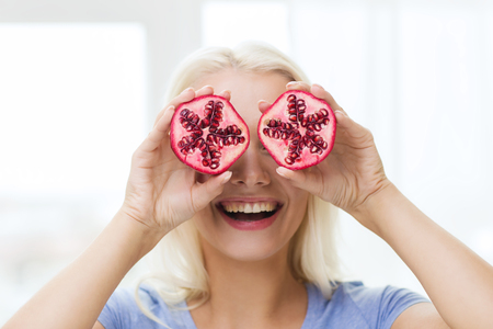 funny face: healthy eating, organic food, fruit diet, comic and people concept - happy woman having fun and covering her eyes with pomegranate