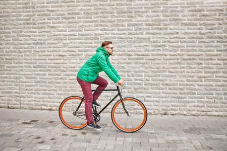 clavados: personas, estilo, ocio y estilo de vida - hombre inconformista joven montar en bicicleta de piñón fijo en la calle de la ciudad sobre el fondo de pared de ladrillo