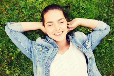 ojos verdes: estilo de vida, vacaciones de verano, el ocio y el concepto de la gente - sonriente joven con los ojos cerrados tumbado en la hierba Foto de archivo