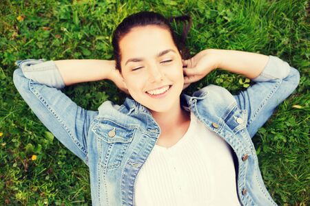 green grass: lifestyle, summer vacation, leisure and people concept - smiling young girl with closed eyes lying on grass Stock Photo