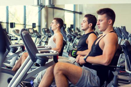 deporte, fitness, estilo de vida, la tecnología y el concepto de la gente - los hombres que se resuelve en la bici de ejercicio en el gimnasio