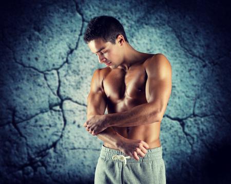 hombres sin camisa: el dolor, el deporte, el culturismo, la salud y el concepto de la gente - culturista masculino joven que toca el codo lesionado sobre el fondo muro de hormigón