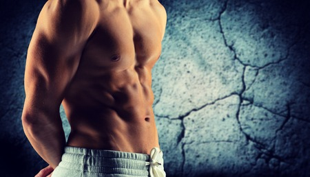 abdomens: sport, bodybuilding, strength and people concept - close up of male bodybuilder bare torso over concrete wall background Stock Photo