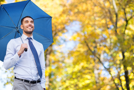 umbrella: business, season, weather and people and concept - young smiling businessman with umbrella over autumn natural background Stock Photo