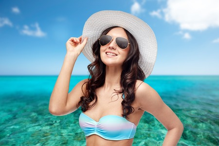 sunstroke: people, summer holidays, travel and tourism  concept - happy young woman in bikini swimsuit, sunglasses and sun hat over sea and blue sky background