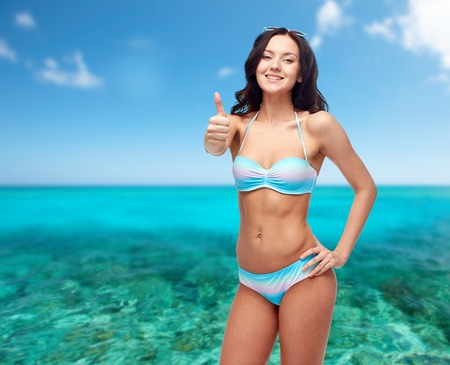 thumbsup: people, summer holidays, travel, tourism and beach concept - happy young woman in bikini swimsuit showing thumbs up gesture over sea and blue sky background