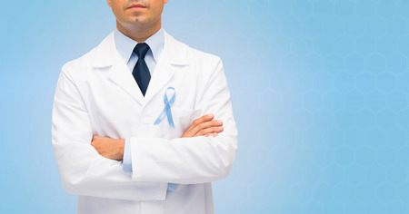oncologist: healthcare, profession, people and medicine concept - close up of male doctor in white coat with sky blue prostate cancer awareness ribbon