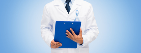 urologist: healthcare, profession, people and medicine concept - close up of male doctor in white coat with sky blue prostate cancer awareness ribbon and clipboard Stock Photo