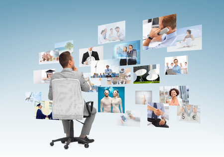 businessman in office: business, people, design and choice concept - businessman sitting in office chair and looking at different images over blue background from back