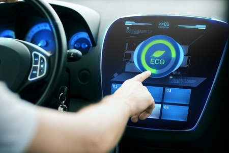 green technology: transport, modern, green energy, technology and people concept - male hand using car eco system mode Stock Photo