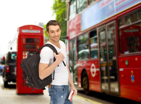 tourists stop: people, travel, tourism and education concept - happy young man with backpack and book over london city bus on street background