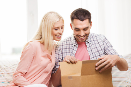 package: people, delivery, shipping and postal service concept - happy couple opening cardboard box or parcel at home