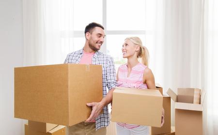cajas de carton: casa, la gente, la reparación y el concepto de bienes raíces - sonriente pareja con cajas de cartón grandes de trasladarse a un nuevo lugar