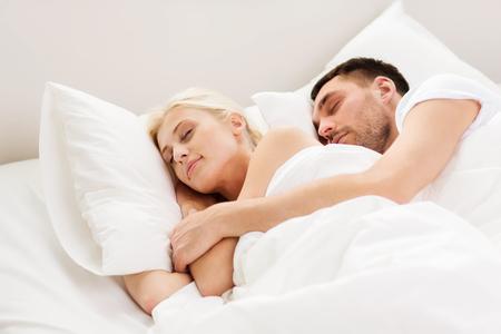 gente durmiendo: las personas, la familia, la hora de acostarse y concepto de la felicidad - pareja feliz dormir y abrazos en la cama en su casa Foto de archivo