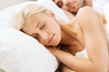 gente durmiendo: personas, de descanso, las relaciones y la felicidad concepto - mujer feliz y el hombre durmiendo en la cama en su casa Foto de archivo
