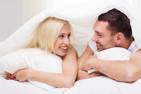 bedtime: people, family, bedtime and happiness concept - happy couple lying in bed covered with blanket over head and talking at home Stock Photo