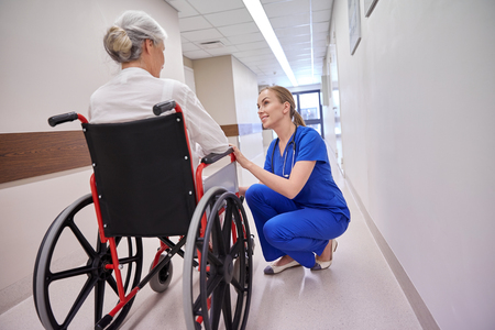 medicine, age, support, health care and people concept - happy nurse talking to senior woman patient in wheelchair at hospital corridor Stock Photo