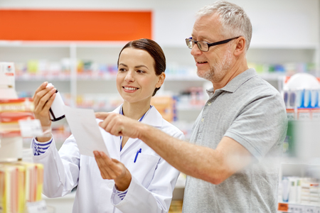 seniors: medicine, pharmaceutics, health care and people concept - happy pharmacist and senior man customer with drug and prescription at drugstore