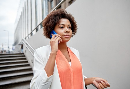 bajando escaleras: business, communication, technology and people concept - young african american businesswoman calling on smartphone going down stairs into city underpass