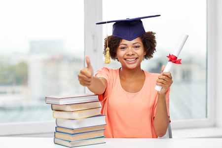 americans: education, school, graduation, gesture and people concept - happy smiling african american student girl in bachelor cap with books and diploma sitting at table and showing thumbs up at home