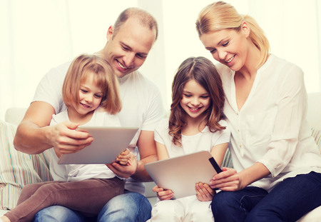 four people: family, children, technology, money and home concept - smiling family and two little girls with tablet pc computers at home