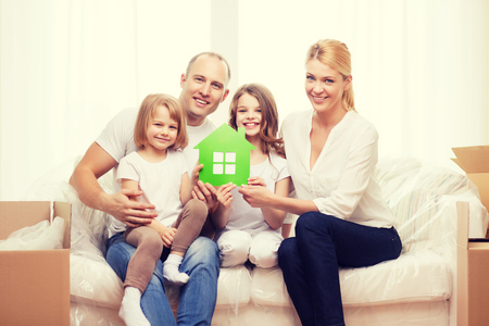 accomodation: family, children, accomodation and home concept - smiling parents and two little girls holding green house