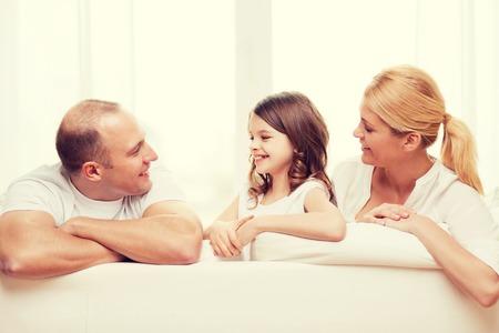 mom dad: familia, niño y el concepto de casa - los padres y la niña sonrientes en casa Foto de archivo