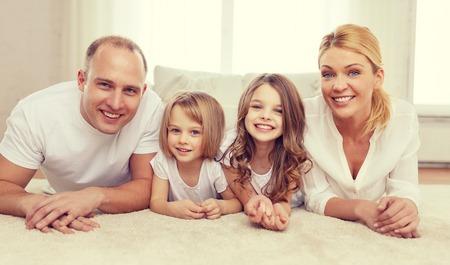 family, children and home concept - smiling family with and two little girls lying on floor at home