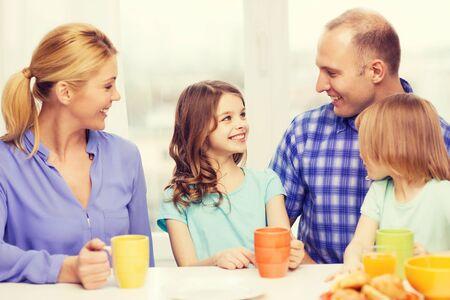 niños desayunando: comida, familia, hijos, la felicidad y el concepto de la gente - familia feliz con dos hijos con desayuno en casa Foto de archivo