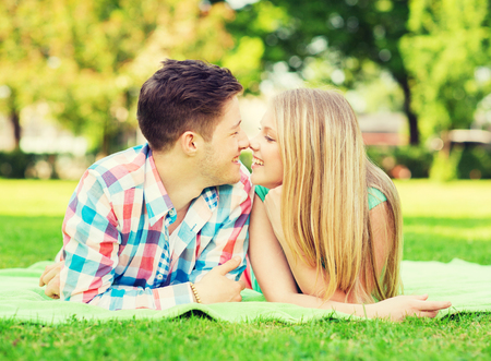 touching noses: holidays, vacation, love and friendship concept - smiling couple lying on blanket and touching noses in park Stock Photo