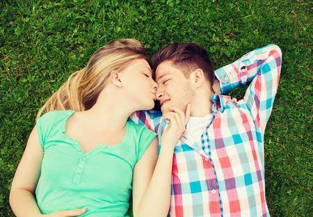 enamorados besandose: días de fiesta, vacaciones, amor y amistad concepto - sonriente pareja acostado en el césped y se besan en parque