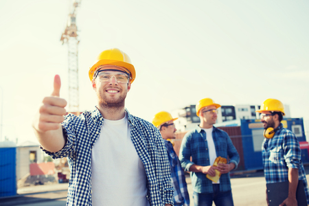 man thumbs up: business, building, teamwork, gesture and people concept - group of smiling builders in hardhats showing thumbs up outdoors
